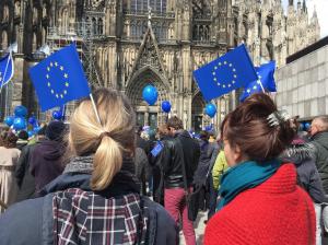 Menschen mit blauen Luftballons und Europa-Fahnen vor dem Kölner Dom zum Pulse of Europe.